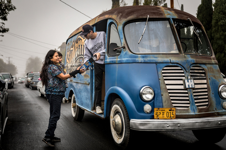 Tony handing out Christmas gifts from the Suavecito Metro Van