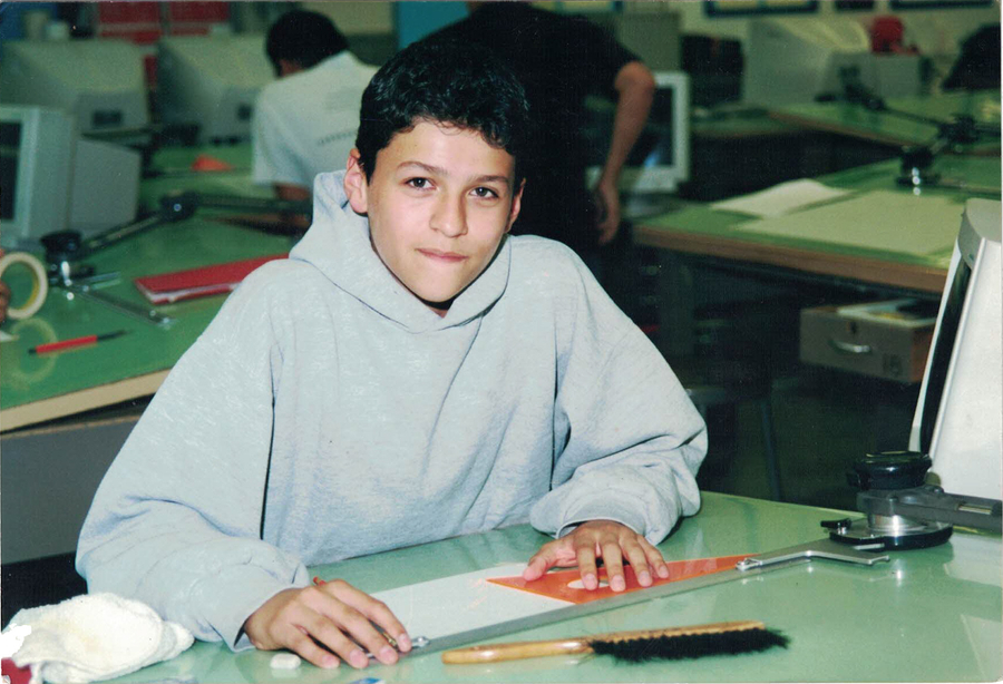 A photograph of Tony in a class room as a child